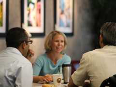 Photo of three people talking over coffee at a table.
