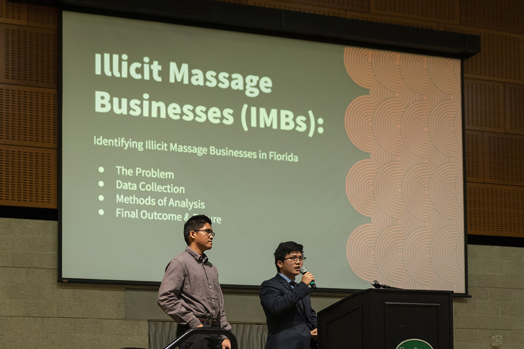Cal Poly statistics majors, and Steven Taruc, left, and Jonathan Shan share details during the CCI's Human Trafficking Summit about their project to collect data on the massage industry in Florida.