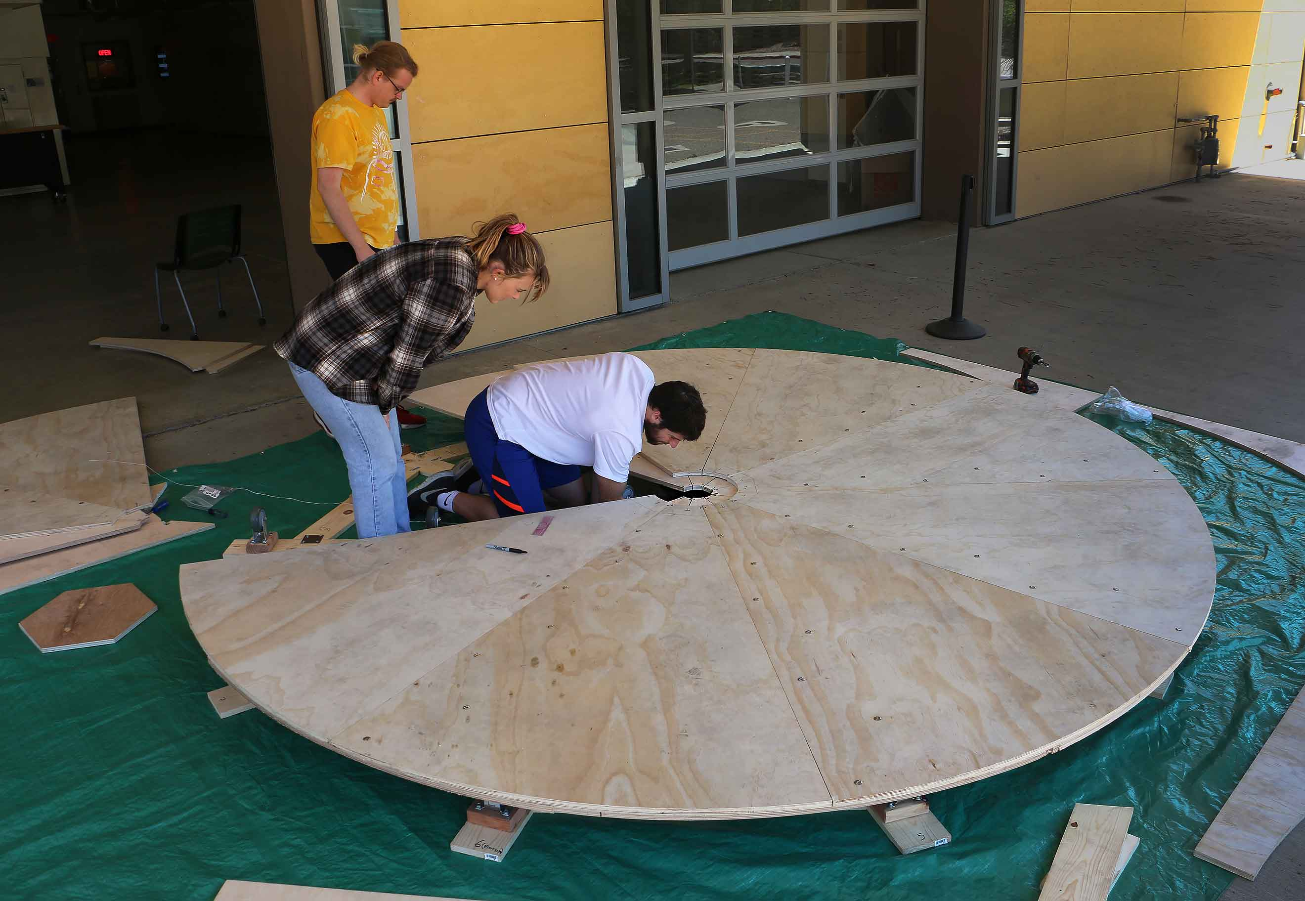 obert Reed, right, works to install a center hub that will make a motorized circular stage rotate. Also helping with the stage, which will be used for a student production later this month, are Isaac Becker, left, and Caroline Whelan, and Liam Martinez (not pictured).