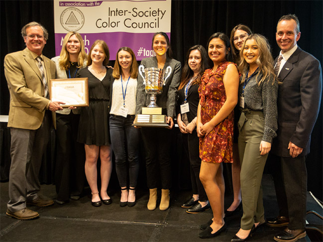 Cal Poly students are awarded the Kipphan Cup at the 2019 TAGA conference in Minneapolis, Minnesota. Pictured from left to right are TAGA President Liam O'Hara, Cal Poly TAGA President Lauren Helms, Erica Taylor, Jessica Rose, Nicole Cullop, Ana Gonzalez, Aileen Vasquez, Kayleigh Macdonald, Hannah Nguyen, and Bruce Leigh Myers, TAGA vice president for education.