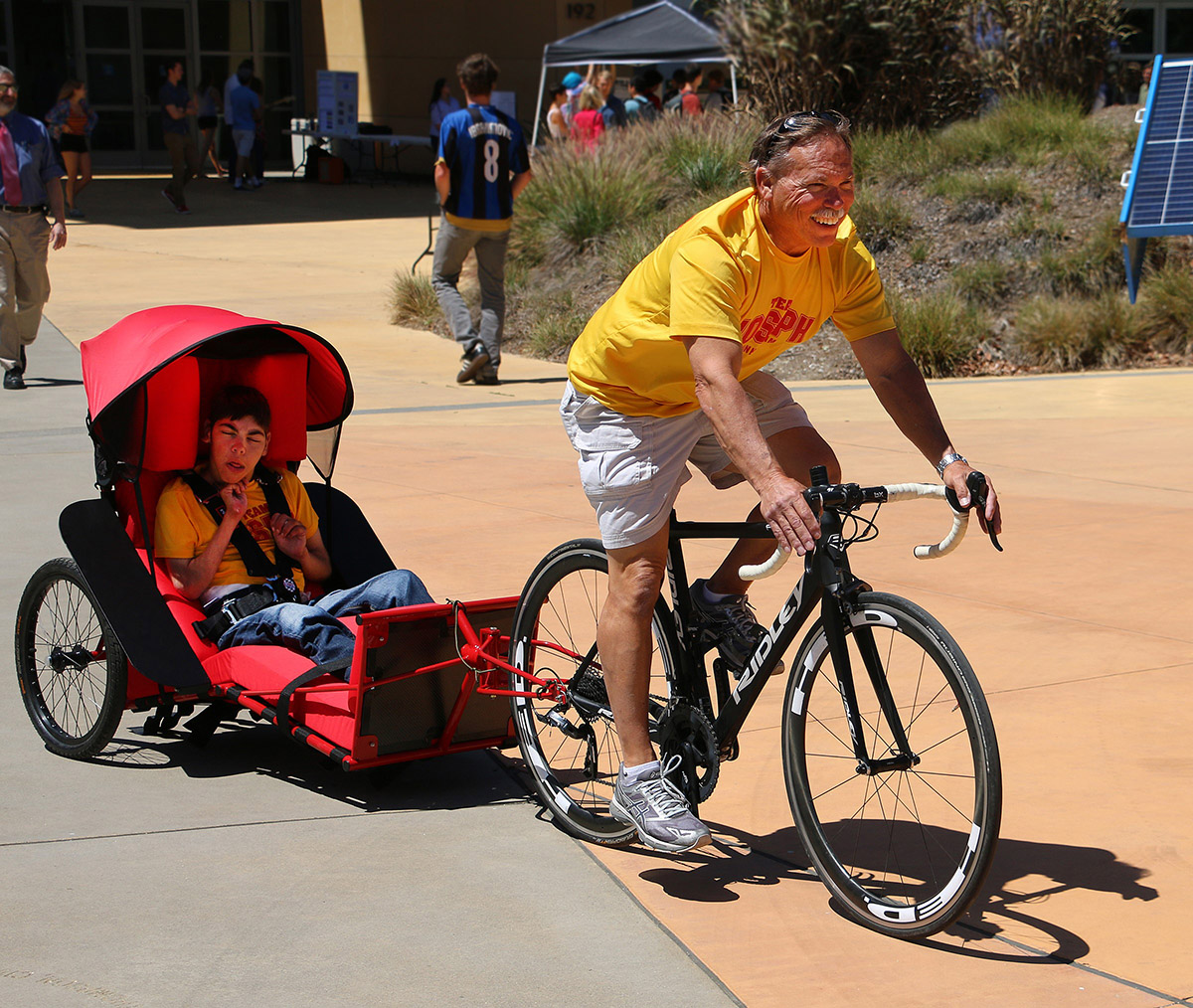 Joseph Cornelius rides in a bike trailer as his father leads the way on a bicycle during the Project Expo. The trailer was designed and built by Cal Poly mechanical engineering students. Father and son will participate in the annual SLO Triathlon on Sunday, July 22.