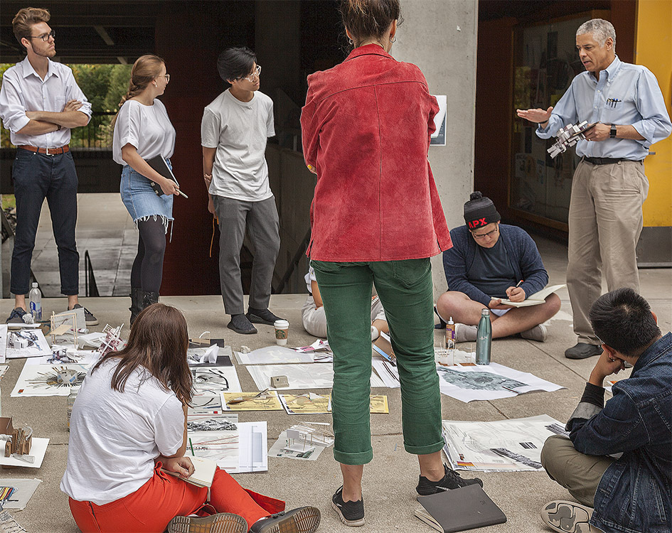 Thomas Fowler, IV, shown right, engages with architecture students outside of their design studio on the Cal Poly campus.