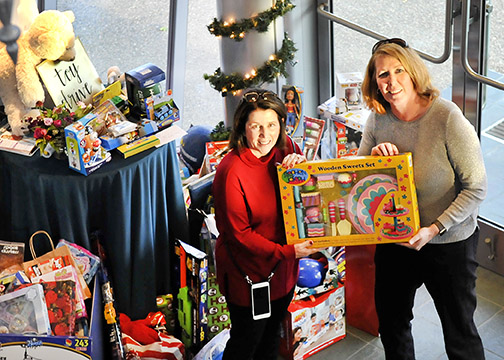 Photo of Mrs. Armstrong and another Cal Poly employee holding a toy that was donated at the 2017 toy drive.