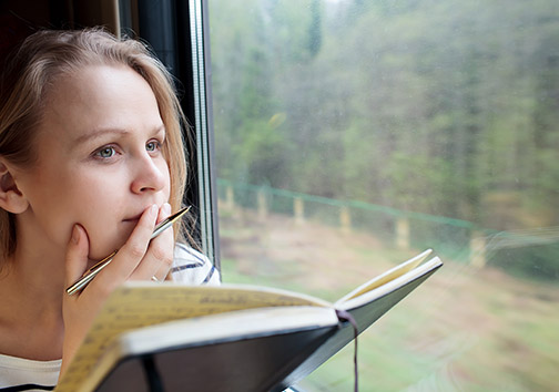Photo of a woman with a notebook and pen in her hand, looking out a window.