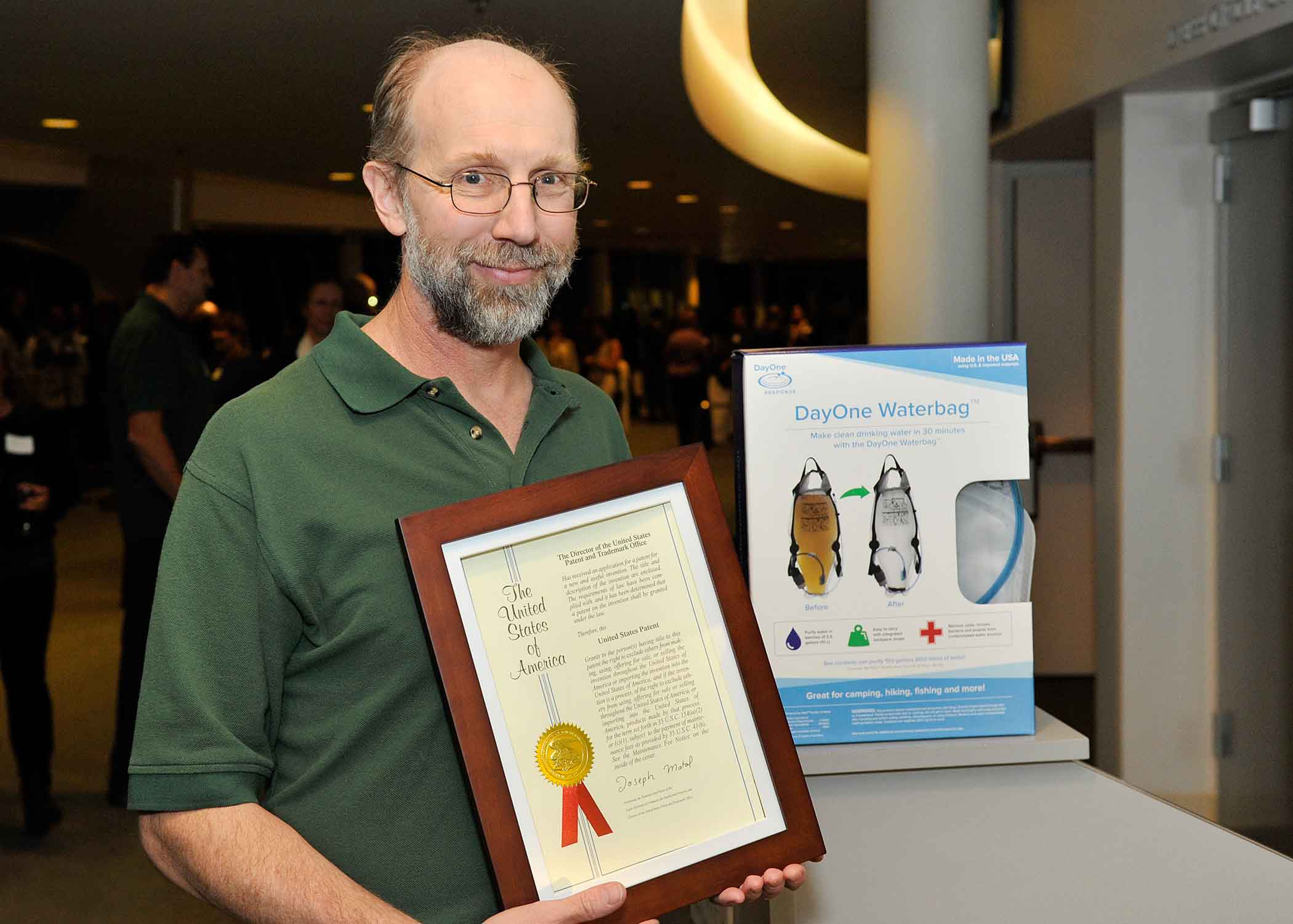 Trygve Lundquist holding his framed patent recognition certificate