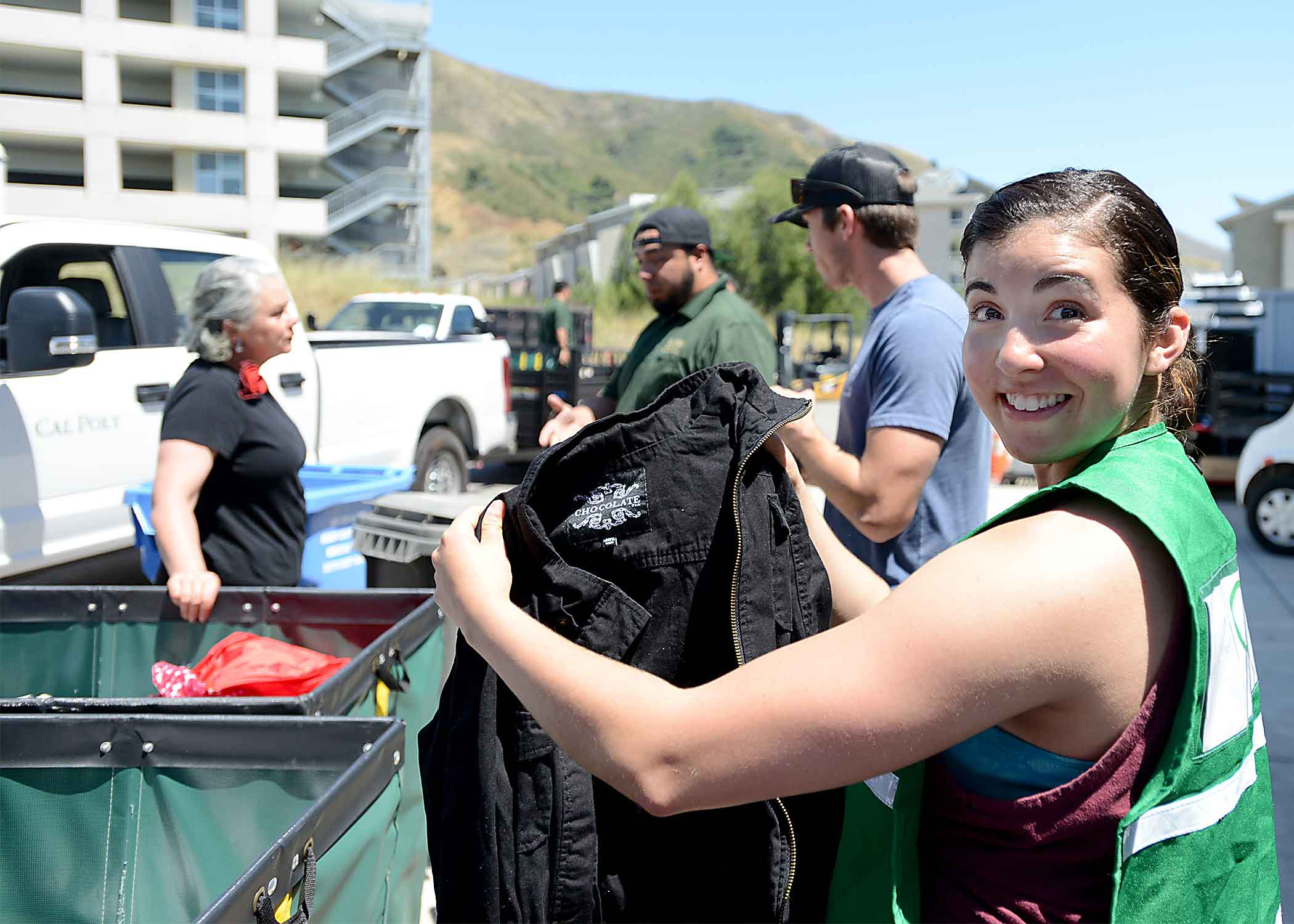 Sydney Sierras, nutrition major from San Jose, helps sort donated clothes as SLO Mayor Heidi Harmon talks to some constituents.