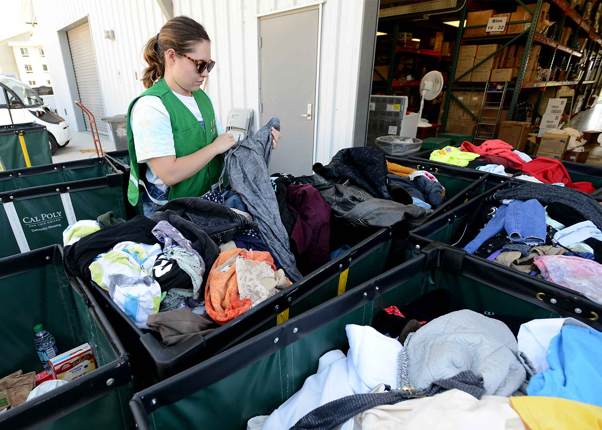 Amanda Smith, a communication studies major from San Diego, helps sort clothes donated by Cal Poly students who lived in campus student housing.