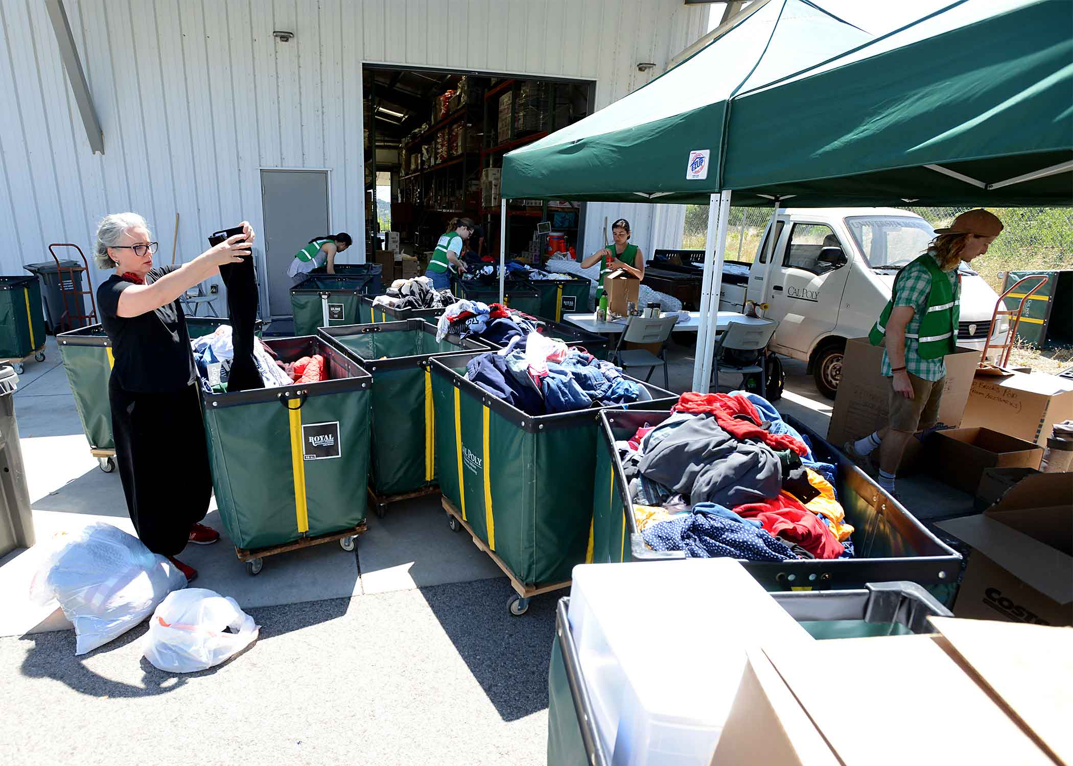 SLO Mayor Heidi Harmon assists student volunteers in sorting clothes donated by Cal Poly students. Also pictured, from left, are Darin Son, Amanda Smith, Sydney Sierras and Adam Simon, a psychology major from San Rafael, California.