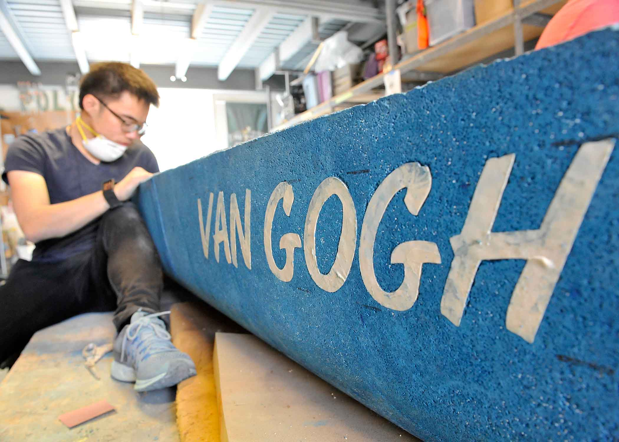 "Jacky Loh, a civil and environmental engineering master's student from Azusa, Calif., sands ""van Gogh,"" this year's entry for the National Concrete Canoe Competition in San Diego. This year's canoe offers a nod to the post-impressionist painter Vincent van Gogh."