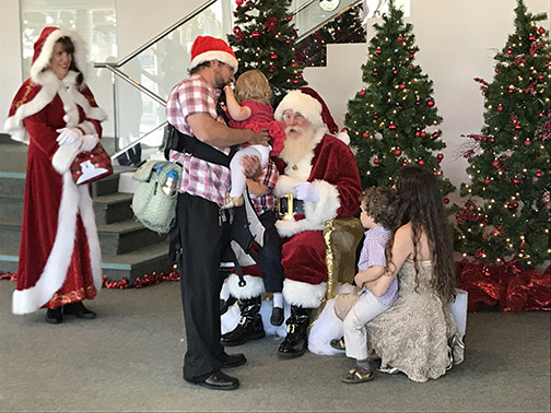 File photo of Santa and Mrs. Claus meeting two children in the Performing Arts Center lobby.