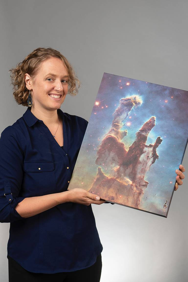 Amherst College astronomy Professor Kate Follette holds an image titled Pillars of Creation, a photograph taken in 1995 by the Hubble Space Telescope of interstellar gas and dust in the Eagle Nebula located some 6,500–7,000 light years from Earth. The gas and dust are in the process of creating new stars, while also being eroded by the light from nearby stars that have recently formed.