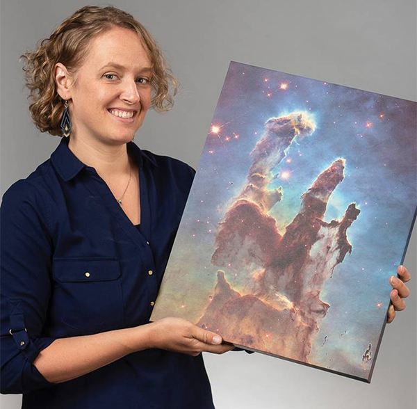 Astronomer Kate Follette holding a photo of a space nebula