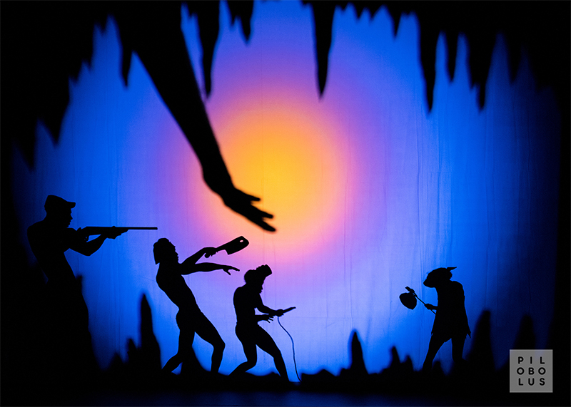 A scene from Shadowland with sillouetted dancers against a purple-yellow backdrop