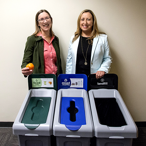 Zero Waste Program Coordinator Anastasia Nicole, left, and Cindy Villa, senior vice president, Administration and Finance, demonstrate the new compose bin in the Administration Building break room.