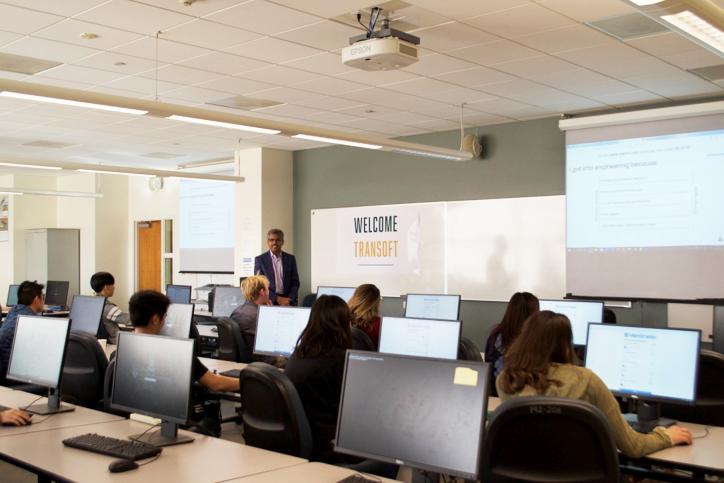 Milton speaks in front of class