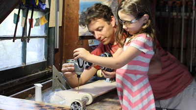 Berger working on a handmade skateboard with his daughter at SK8Makers HQ (aka the garage workshop).