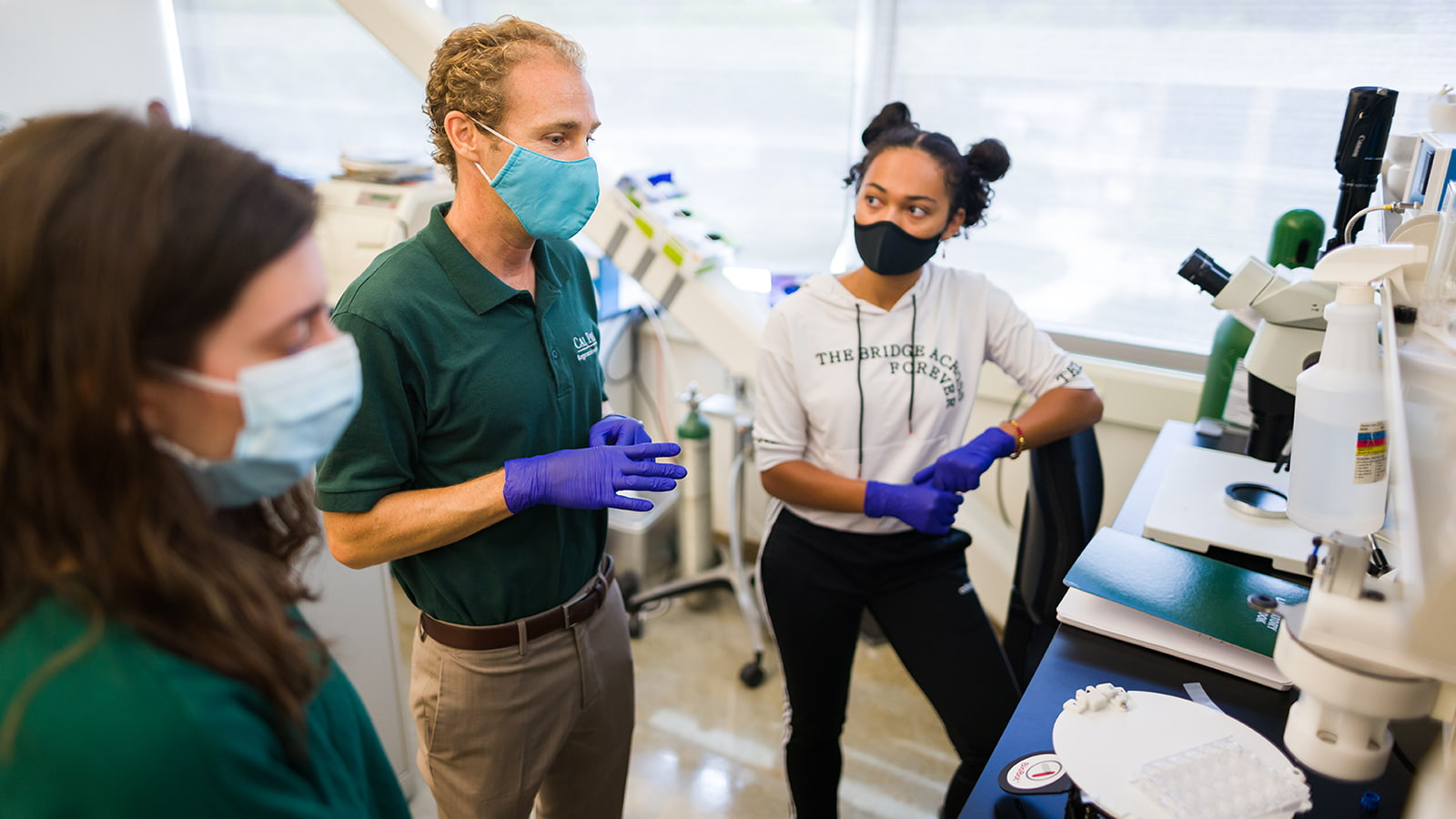 Professors and student wearing masks in the SURP lab at Cal Poly