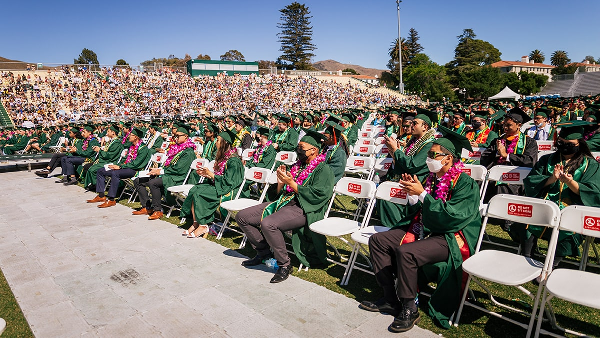 Masked and/or socially distanced students attend an outdoor graduation ceremony