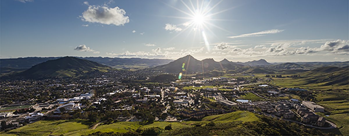 Aerial view looking west across the cerro hill tops with a sunburst in the sky