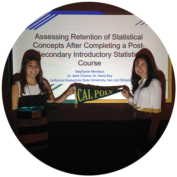 ephanie Mendoza and Noelle Pablo caring a Cal Poly flag while they are giving a presentation.
