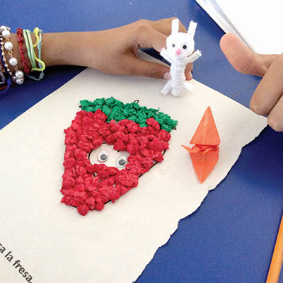 An arts and craft piece making a strawberry shape on paper.