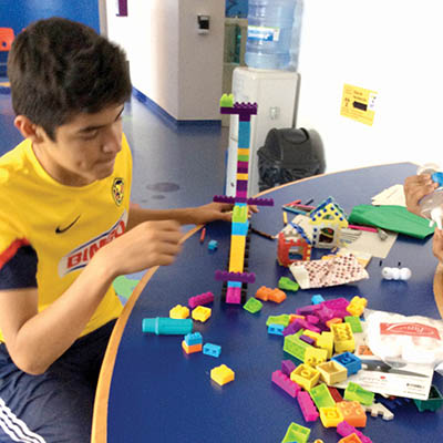 A teenage boy constructing a tower out of building blocks.