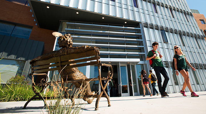 Stock image. Iconic statue foreground. Student exiting William J. Baker Center for Science and Mathematics.