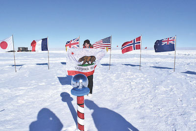 Lesley Anderson holds the California state flag signed by her students at the ceremonial South Pole marker.