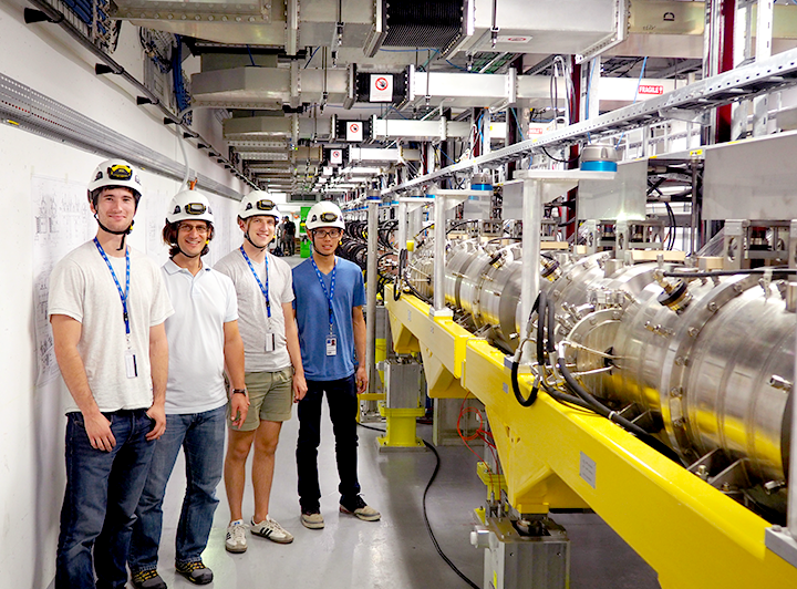 Themis Mastoridis and three of his students are standing in a long room full of metal pipes.
