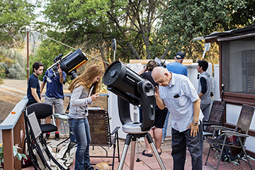 Students, mentors look through at telescope from an outdoor deck