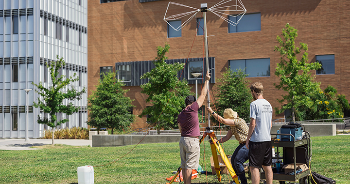 Students erect an antenna outside the Baker Center