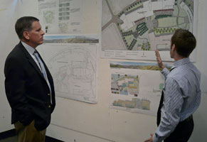 President Armstrong watches a student presentation of his design
