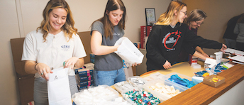Cal Poly students Lucy Passaglia and Amelia Johnson, alumna Tayler Garis and biological sciences Professor Candace Winstead set up for a syringe exchange and overdose prevention program at the San Luis Obispo County Public Health Department.