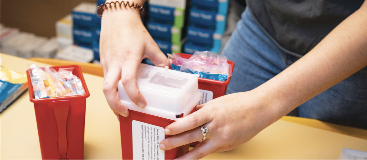 Student packing a container with sterile syringes and other supplies.