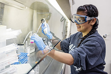 Photo of woman wearing gloves and using lab equipment