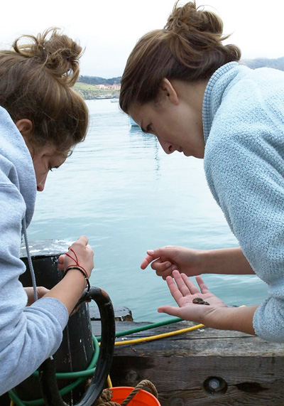 Two girls examining a rock on a boat.