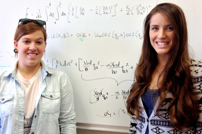 two female students in front of a white board with equations on it