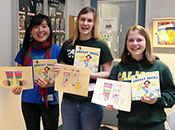 Cal Poly students holding children's books and art projects