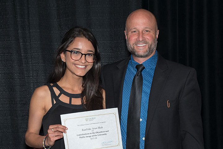 Raadhika Shah holds her certificate and stand with Dean Wendt