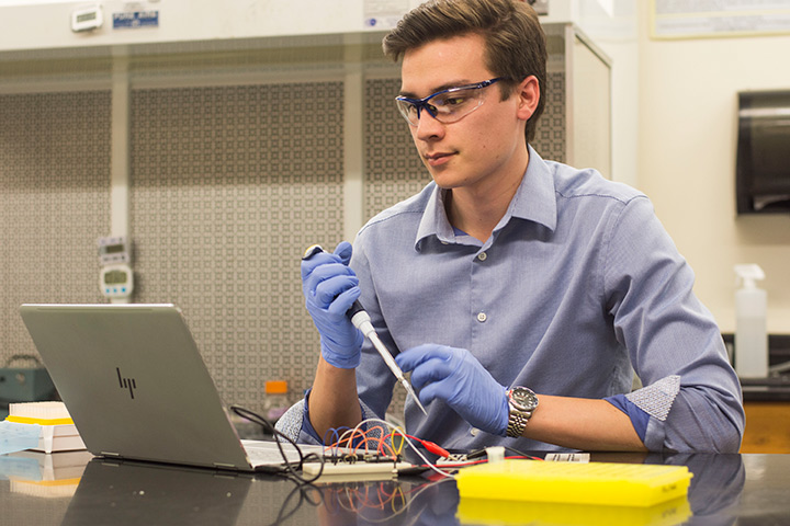 Brandon Strong analyzes experimental results in the lab holding pipette and looking at computer