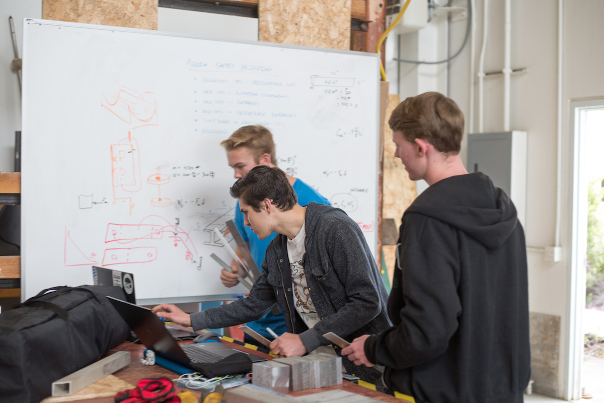 Students gather around a white board to workout problems for their prototype.