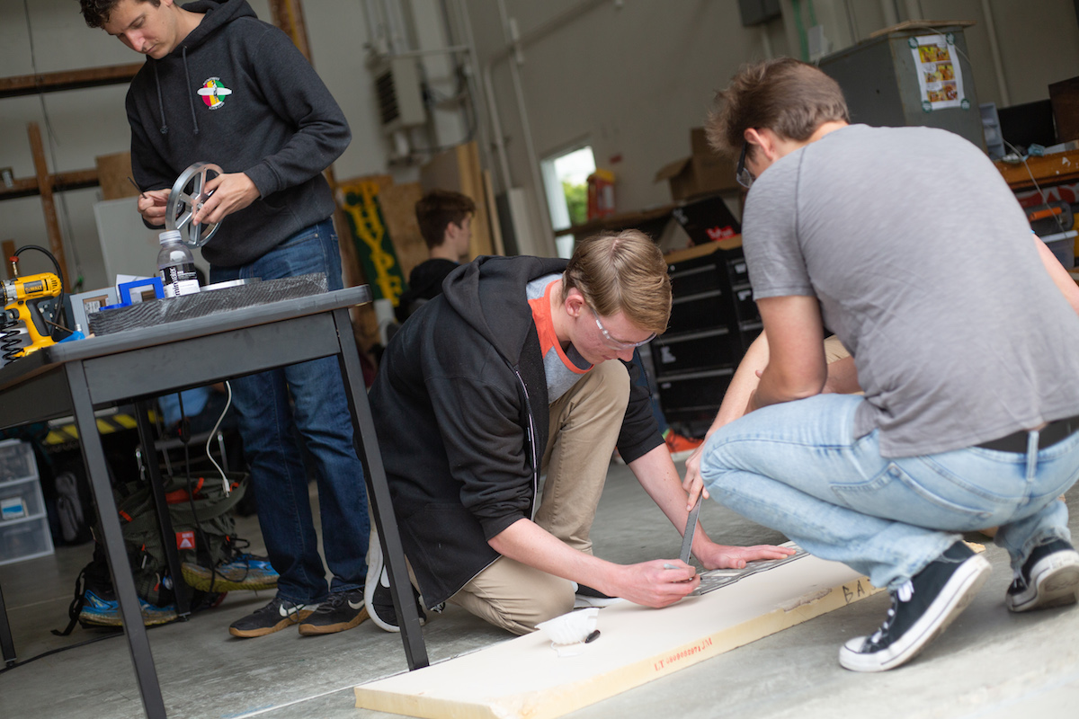 Three students taking measurements and cutting wood.