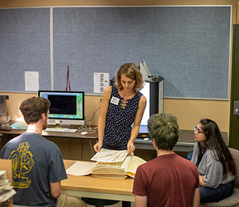 Staff and students examine dried plants in the university herbarium