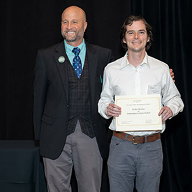 Jordan Rowley holds his certificate and stands with Dean Wendt