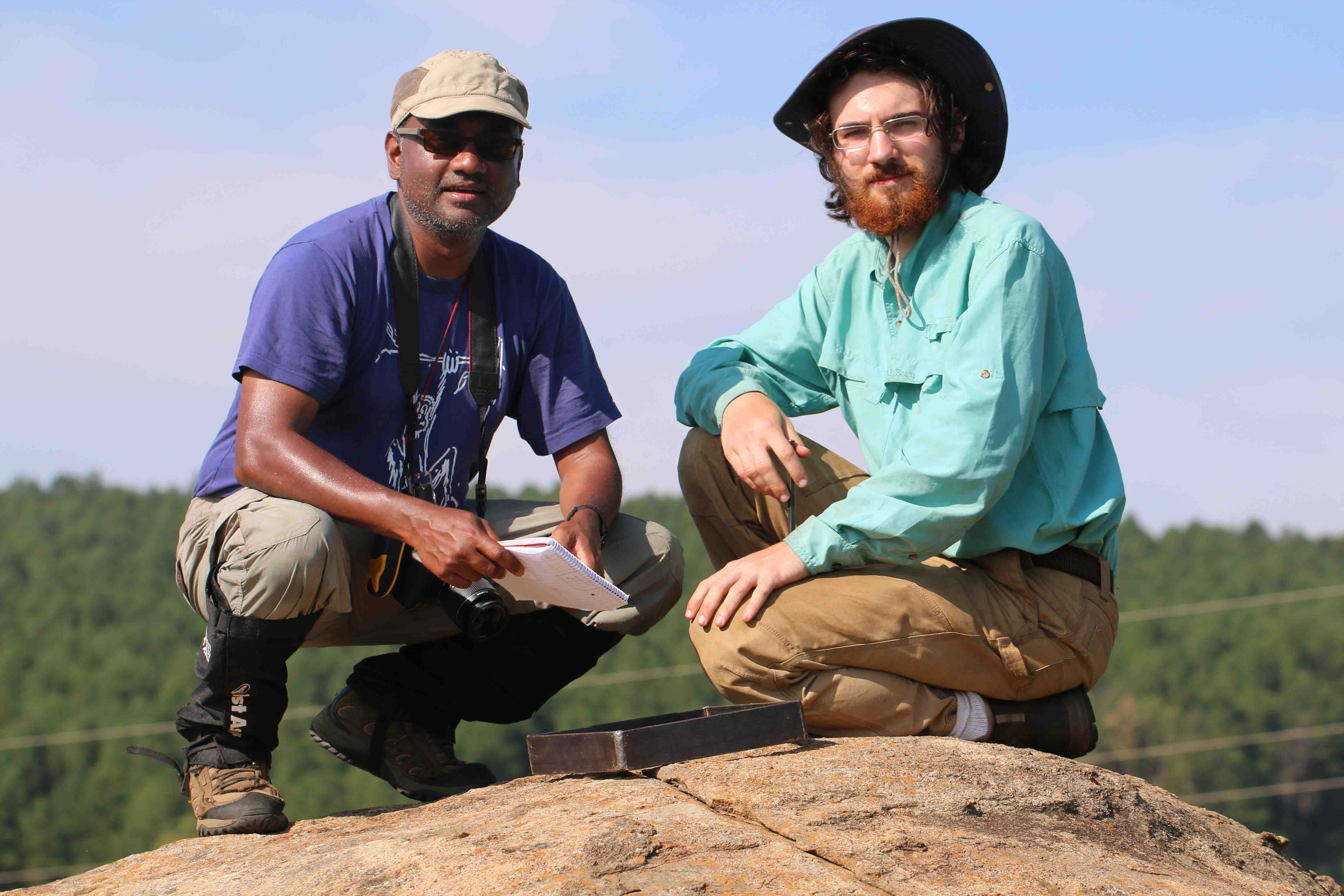 Nishi Rajakaruna (left) and Ian Medeiros collect lichen specimens on an outcropping of the rock serpentinite during an expedition in eastern South Africa.