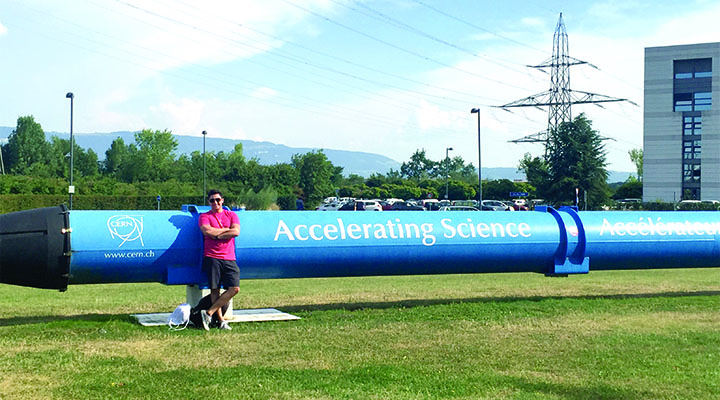 Austin Guard leans against a large and long blue pipe called a superconducting dipole magnet