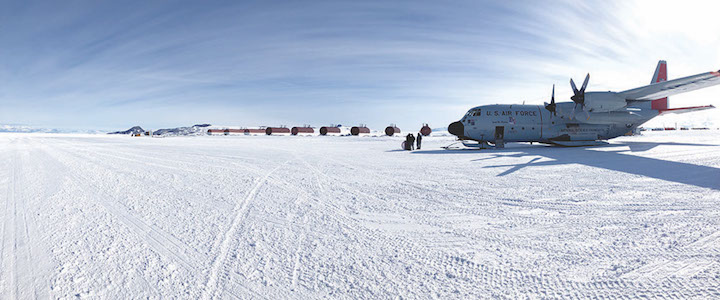 A giant plane sits in an open snow field, ready for take off.