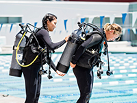 Student helps another fit her scuba tank