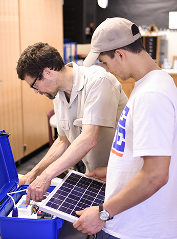 image. physics Professor Pete Schwartz and a student assemble the solar suitcase