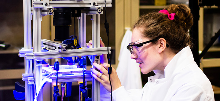 Student in a lab coat working on a piece of equipment consisting of multiple metal bars connected to make a 3-D column